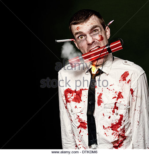 Zombie Suicide Bomber Holding A Mouthful Of Dynamite While Initiating A Halloween Zombie Apocalypse On Dark Studio - Stock Image