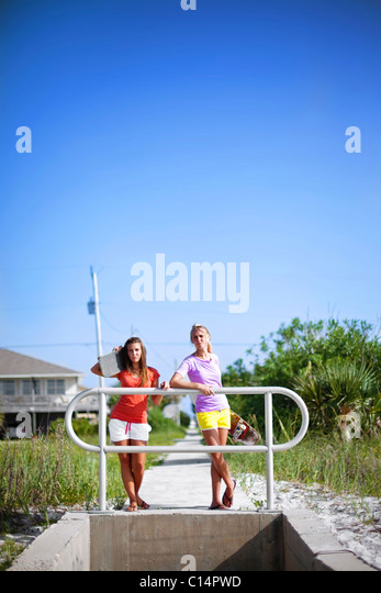Two girls rest with their skateboards as they look out over the Santa Rosa Sound in Pensacola Beach, Florida. - Stock Image