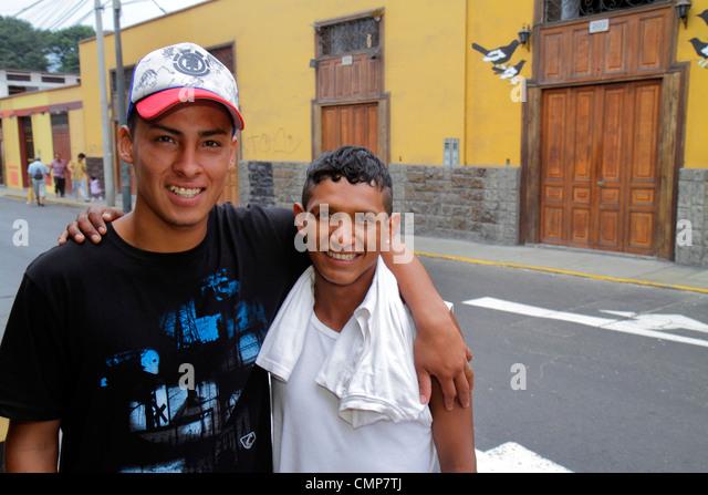 Lima Peru Barranco District Calle 28 de Julio neighborhood street scene Hispanic boy teen friends embracing taller - Stock Image