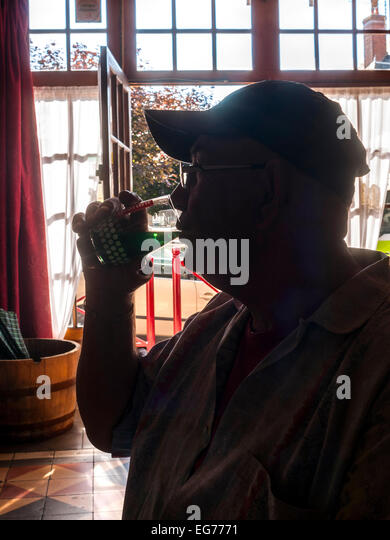 Silhouette of man drinking in bar - France. - Stock Image