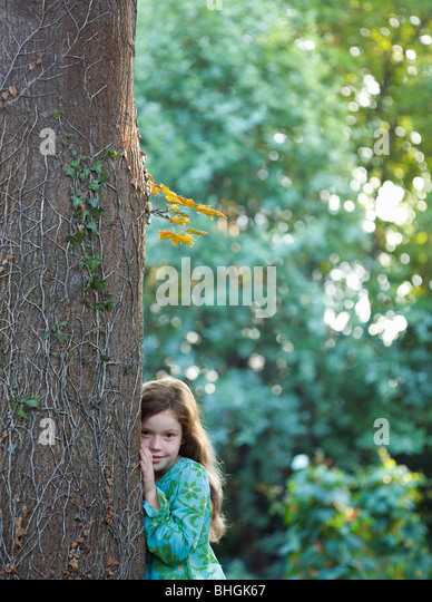 Young girl leaning on tree in garden - Stock Image