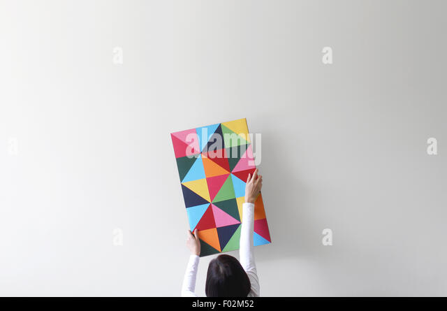 Woman decorating an empty white wall with colorful artwork - Stock Image