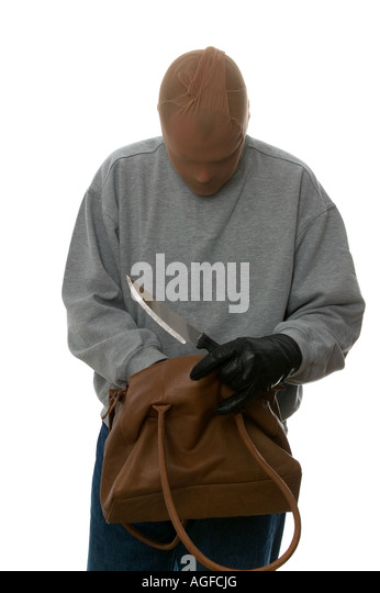 Mugger with a knife searching through a handbag from his latest victim - Stock Image