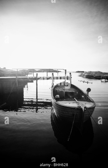 Boat by a jetty against the light, Sweden. - Stock Image