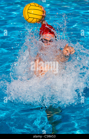 Water Polo explodes out of the pool and directs team mate for a pass. - Stock Image