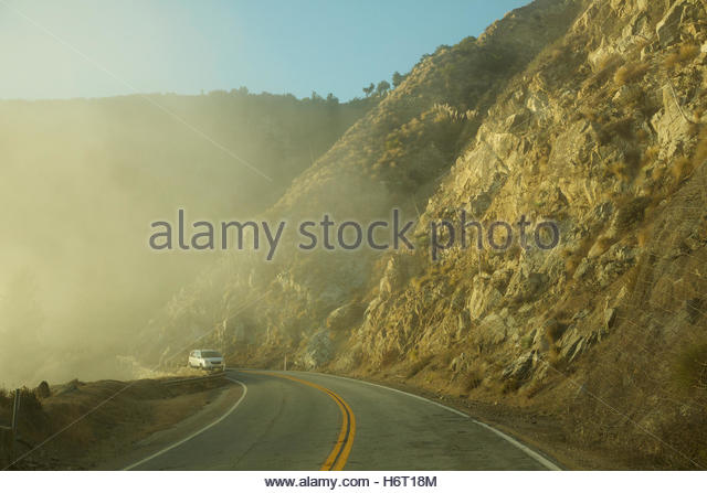 A minivan drives along the Big Sur coast in the fog. - Stock Image