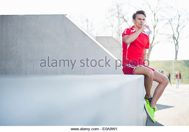 Mid adult male runner drinking bottled water in park - Stock Image