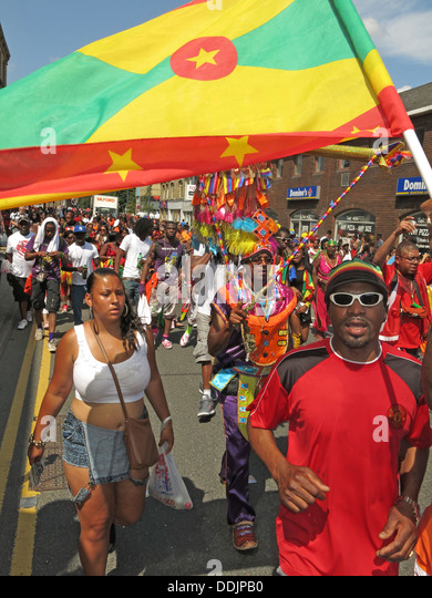 Costumed dancers holding flag from Huddersfield Carnival 2013 African Caribbean parade street party - Stock Image