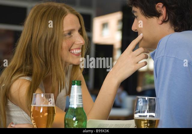Young couple in cafe, woman touching man's cheek - Stock-Bilder