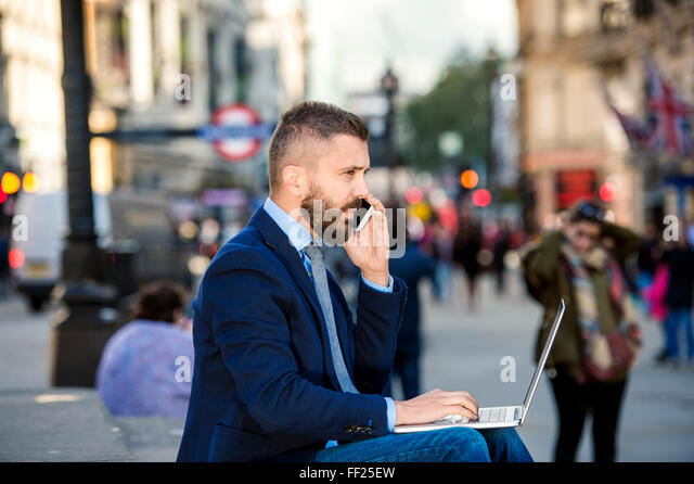 Manager with laptop and smart phone, sunny Piccadilly Circus, Lo - Stock-Bilder