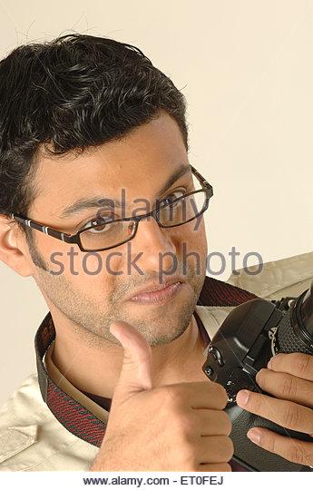 Photographer using still SLR camera strap around neck showing thumb MR#748L - Stock Image