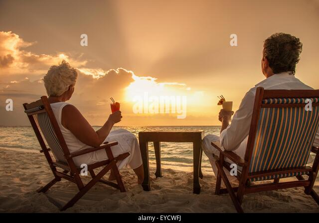 Senior couple with drinks on beach, Maldives - Stock Image