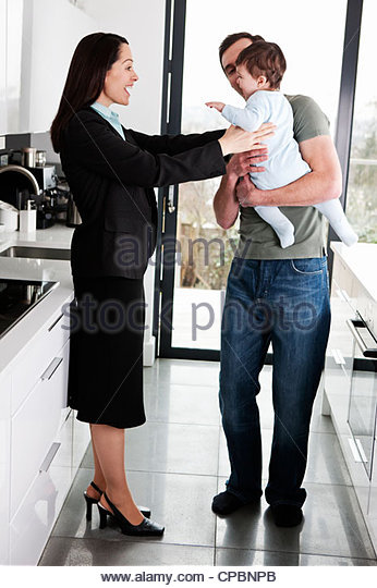 A working mother greeting her partner and baby son - Stock-Bilder
