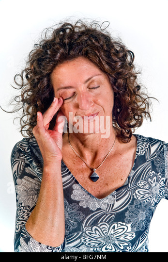 Rubbing her eye indicates a mood of doubt and disbelief in this woman in body language terms. - Stock Image