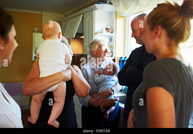 Family gathered in kitchen at home - Stock-Bilder