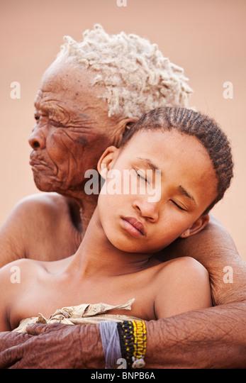 Bushman/San People. Young girl with old woman embracing - Stock-Bilder