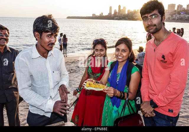 Mumbai India Asian Girgaon Marine Drive Chowpatty Beach public vendor roasted corn on cob man woman Hindu Arabian - Stock Image