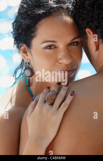 Honeymoon: happy young newlyweds smiling and relaxing near hotel pool. Vertical shape, head and shoulders - Stock Image