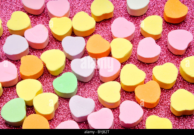 Valentines day candy on pink sparke surface - Stock Image