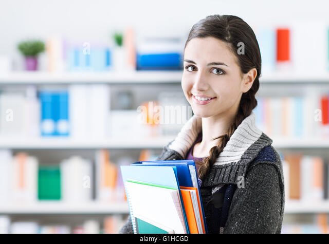Smiling young student girl posing in the school library, she is holding notebooks and looking at camera - Stock Image