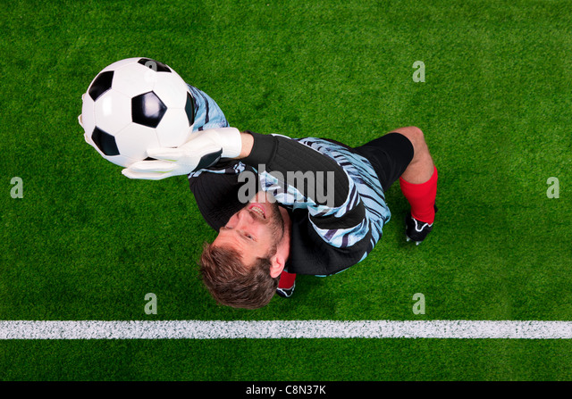 Overhead photo of a football goalkeeper jumping in the air saving the ball on the line. Focus point is on his face. - Stock Image