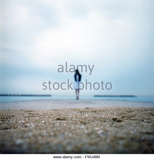 Woman Standing At Beach Against Sky - Stock Image