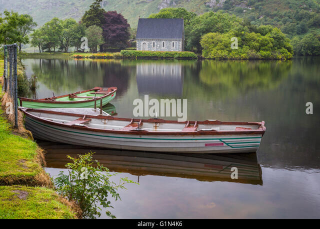 Gougane Barra, County Cork, Republic of Ireland.  Eire.  Looking across rowing boats moored at the lake shore with - Stock Image
