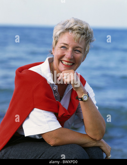 outside woman smile middle age old person senior citizen summer portrait sea contently - Stock Image