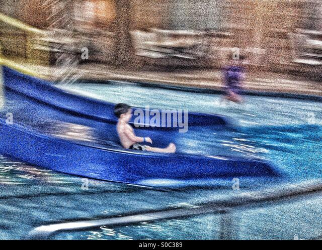 Action Blur of a Boy Sliding at a Water Park - Stock Image