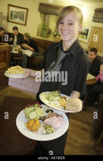 England UK Yorkshire Dales National Park Burnsall Red Lion Hotel restaurant waitress server food plate - Stock Image