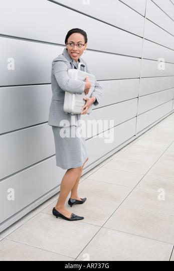African businesswoman clutching briefcase - Stock-Bilder