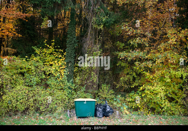 Garbage bags and compost bin in wooded landscape - Stock Image