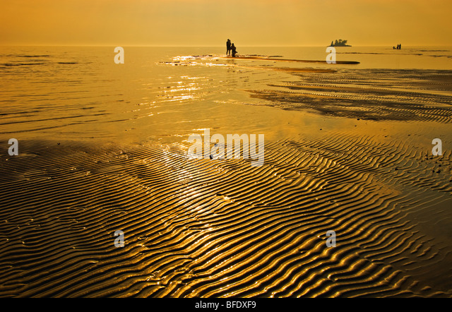 People on the beach at sunset, Wahnekewaning Beach, Ontario, Canada - Stock Image