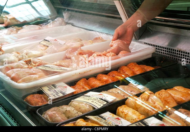 Hand handling Raw Pieces of Chicken - Stock Image