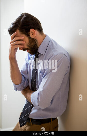 Depressed man with hand on forehead - Stock Image
