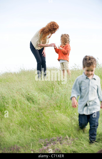 Little girl giving mother wildflowers - Stock Image