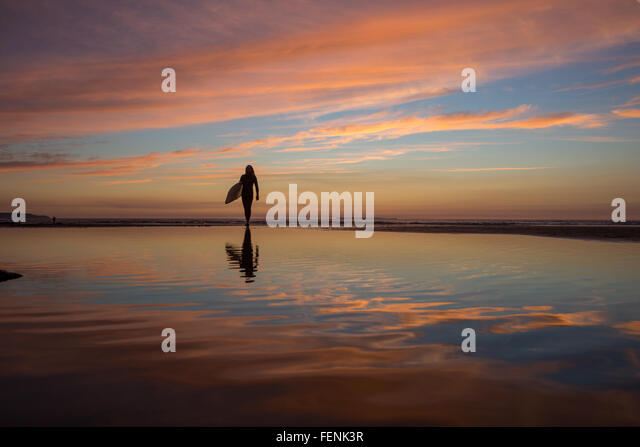 tranquil surfer reflects on the days surfing at Westward Ho! Beach in Devon - Stock Image