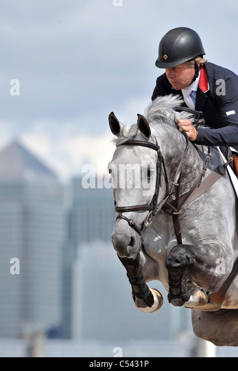 Nick Skelton (GBR) riding Carlo with Canary Wharf in the background. Show Jumping Demonstration Competition. Greenwich - Stock Image
