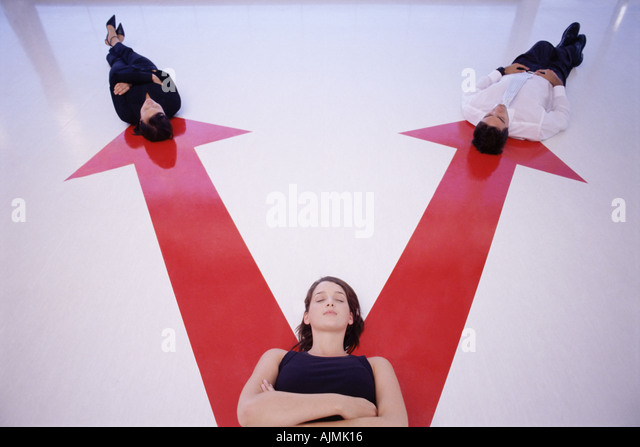 Three people lying on arrow signs - Stock Image