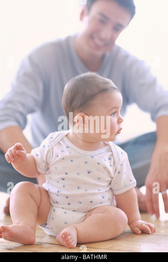Baby boy and father.6-month-old baby boy sitting down with his father. - Stock Image