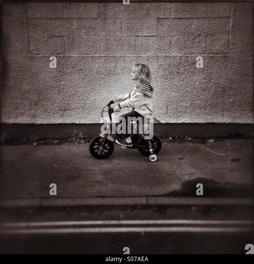 Kid on a bike with stabilisers - Stock Image