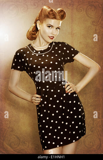 Pin-Up girl in classic fashion polka dots dress posing - grunge - Stock Image