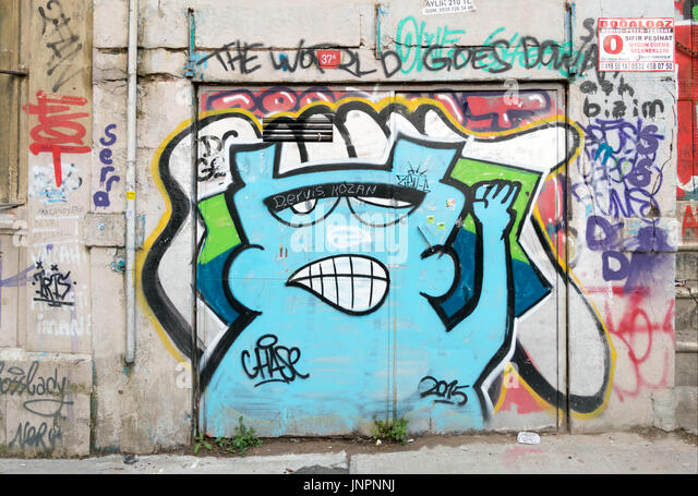 Closed shop exterior with metal door covered with colorful graffiti near Istiklal Street, Istanbul, Turkey - Stock Image