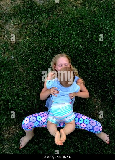 Girl lying down on the grass outside with her brother - Stock Image