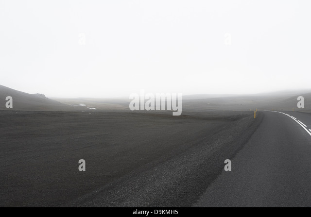 Grey road in empty landscape - Stock Image