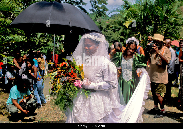 Bride with woman holding her wedding dress train Tobago Heritage Festival old time wedding at Moriah village ole - Stock Image
