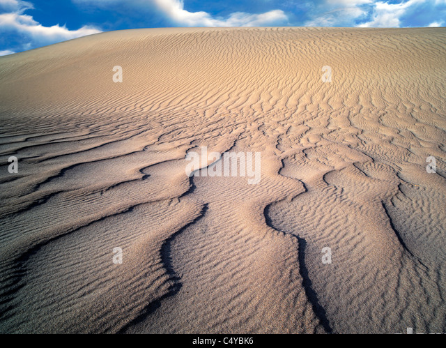 Wind ripples in sand dunes. Death Valley National Park, California. Sky was added - Stock Image