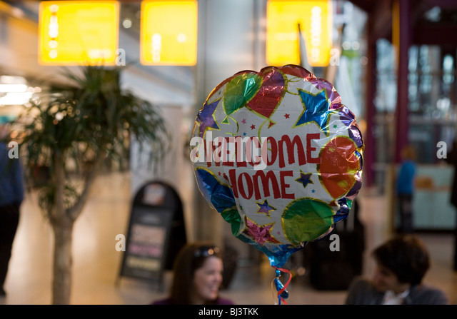 A helium-filled Welcome Home balloon floats in the air in Heathrow Airport's Terminal 5 arrivals hall. - Stock-Bilder
