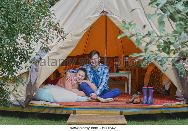Young couple sitting in tent together. - Stock Image