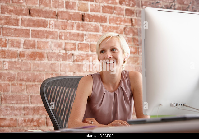 Portrait of mid adult woman at desk with brick wall - Stock Image